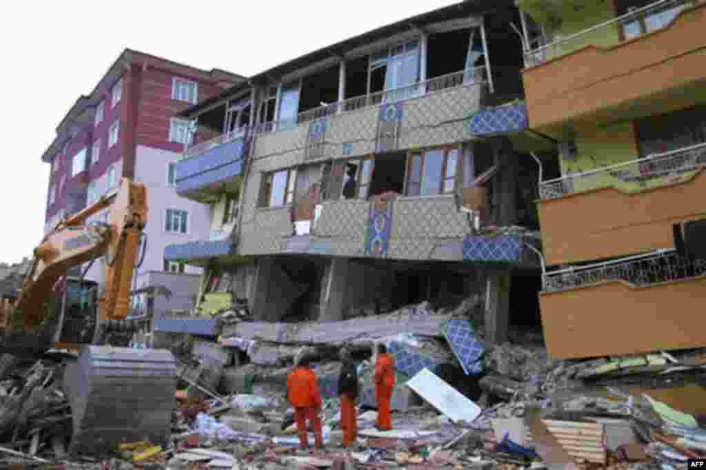 In this Wednesday, Oct. 26, 2011 photo, rescue workers examine the quake-toppled multistory Buse Cafe, center, in the worst-hit town of Ercis in Van province, Turkey. The magnitude-7.2 quake that struck Oct. 23 has killed more than 600 people, including 6