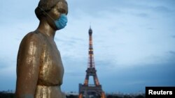 Zlatna statua sa zaštitnom maskom na licu na Trgu Trokadero, u blizini Ajfelove kule u Parizu (Foto: Reuters/Benoit Tessier)