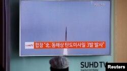 乘坐韩国首尔火车的乘客正在观看朝鲜向日本海发射三枚弹道导弹的新闻(2016年9月5日)
