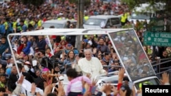 Pope Francis greets the crowd of faithful from a popemobile in Quito, Ecuador, July 5, 2015.