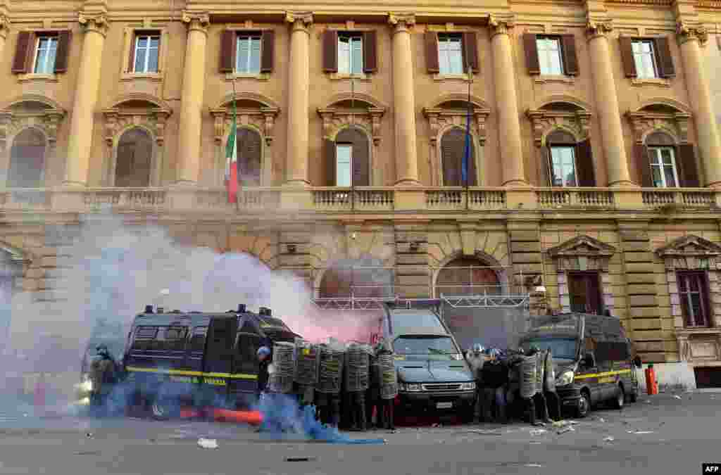Members of the Guardia di Finanza protect themselves as they stand in front of the Economy ministry during clashes on the sidelines of an anti-austerity protest in Rome, Italy.