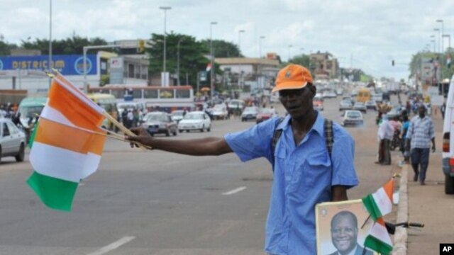 A street vendor sells Ivorian flags and portraits of Ivory Coast President Alassane Ouattara at a market in Yamoussoukro on May 20, 2011, before his investiture ceremony which is due to be held on May 21, 2011.