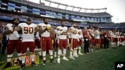Los jugadores de los Washington Redskins permanecen de pie durante la interpretación del himno nacional ante del primer partido de la pretemporada de la NFL ante los Patriots de Nueva Inglaterra el jueves, 9 de agosto de 2018 en Foxborough, Massachusetts.