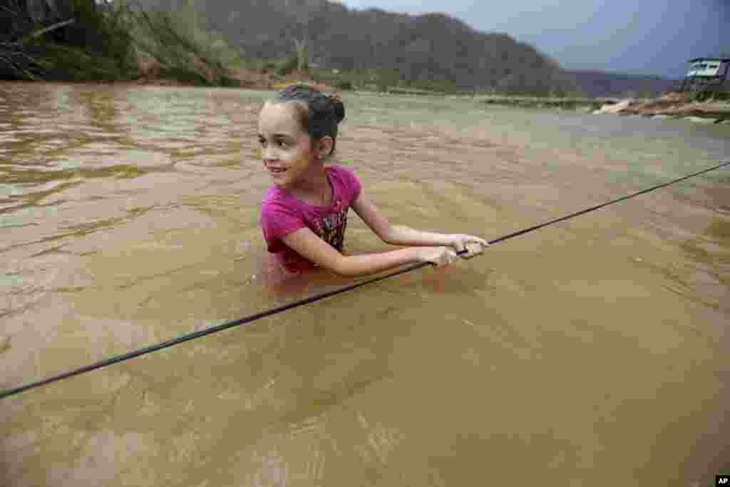 Ruby Rodriguez, 8, looks back at her mother as she wades across the San Lorenzo Morovis river with her family, since the bridge was swept away by Hurricane Maria, in Morovis, Puerto Rico, Sept. 27, 2017.