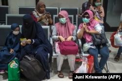 Penumpang yang mengenakan masker di tengah kekhawatiran penyebaran COVID-19 menunggu untuk naik kereta di stasiun kereta di Surabaya pada 15 Maret 2020. (Foto: Juni Kriswanto/AFP)