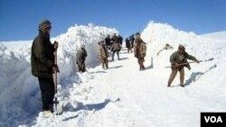 Des Afghans mettent en neige sur le côté d'une route pour déblayer le passage, en Afghanistan, le 5 février 2017. (VOA)