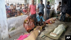 An elderly woman grieves next dead bodies at Mymensingh Medical College Hospital in the town of Mymensingh, Bangladesh, July 10, 2015.