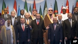 Turkey's President Recep Tayyip Erdogan, center, gestures following a photo-op prior to the opening session of the Organisation of Islamic Cooperation Extraordinary Summit in Istanbul, Wednesday, Dec. 13, 2017. From left, front row, Kuwait's Emir Sheikh Sabah Al Ahmad Al Sabah, Jordan's King Abdullah II, Erdogan, Palestinian President Mahmoud Abbas and Azerbaijan's President Ilham Aliyev. (Arif Hudaverdi Yaman/Pool Photo via AP)