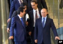 Japanese Prime Minister Shinzo Abe, left, and Russian President Vladimir Putin come down on the escalator after their talks in Vladivostok, Russia, Friday, Sept. 2, 2016.