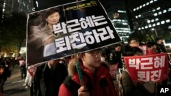 FILE - A South Korean protester carries a placard showing images of South Korean President Park Geun-hye and Choi Soon-sil, top left, during a rally calling for Park to step down, Nov. 2, 2016.