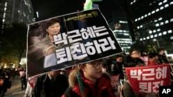 ក្រុមបាតុករកាន់រូបលោកស្រីប្រធានាធិបតី Park Geun-hye និងលោក Choi Soon-sil ក្នុងពេលបាតុកម្មឲ្យលោកស្រីប្រធានាធិបតីចុះចេញពីតំណែង កាលពីថ្ងៃទី២ ខែវិច្ឆិកា ឆ្នាំ២០១៦ ក្នុងក្រុងសេអ៊ូល ប្រទេសកូរ៉េខាងត្បូង។