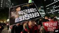 FILE - A South Korean protester carries a placard showing images of South Korean President Park Geun-hye and Choi Soon-sil, top left, during a rally calling for Park to step down, Nov. 2, 2016, in Seoul, South Korea.