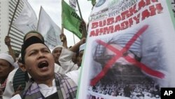 Indonesian Muslims display a defaced poster of Mirza Ghulam Ahmad, the prophet of Ahmadiyah, during a protest demanding ban of the Muslim sect in Jakarta, Indonesia, March 1, 2011