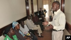 A health worker speaks to HIV patients waiting for treatment in Kampala, Uganda