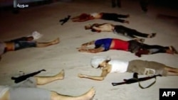 An image grab taken from a broadcast on Syrian television on July 20, 2012, shows dead men lying on the ground next to weapons in the Teshrin neighborhood of the Qabun area in Damascus. (AFP Photo / Ho / Shaam News Network)