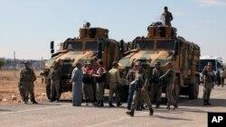 지난 29일 터키-시리아 국경 지역에서 터키군 병사들이 쿠르드계 터키 주민들과 대화하고 있다.