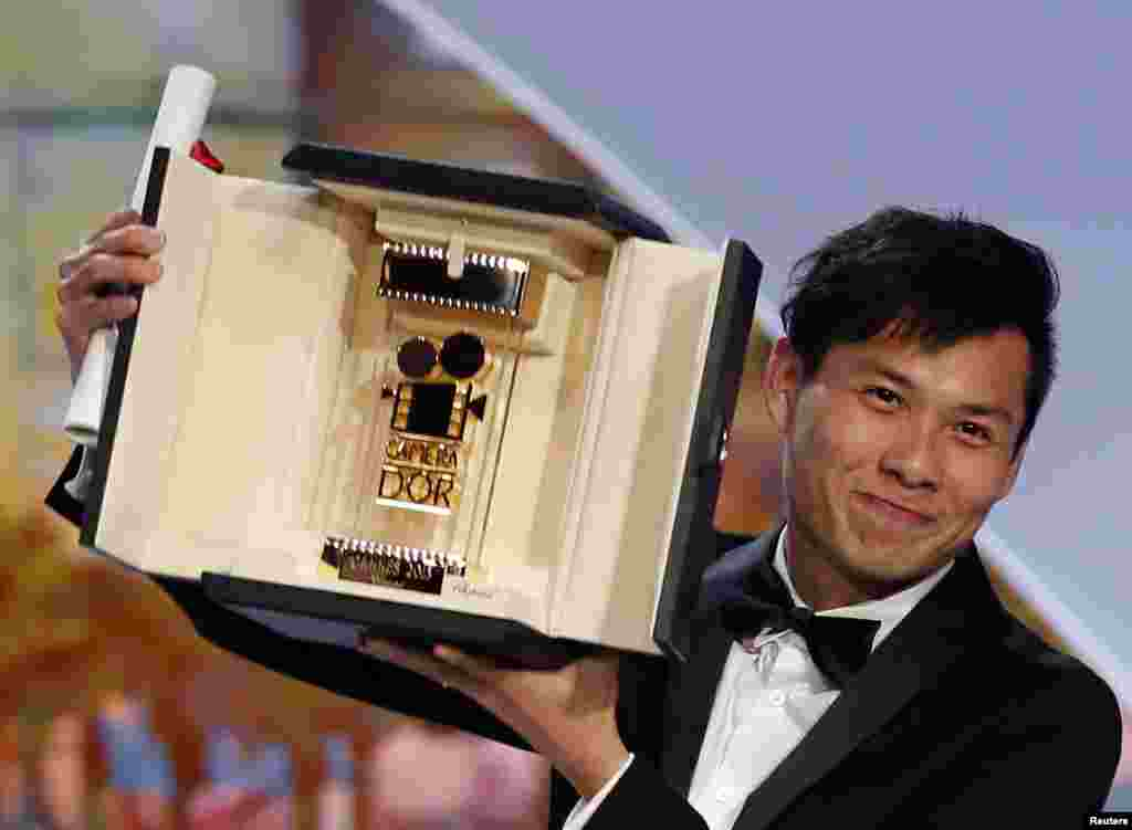 """Director Anthony Chen, Camera d'Or award winner for the film """"Ilo Ilo"""", poses on stage during the closing ceremony of the 66th Cannes Film Festival, May 26, 2013."""