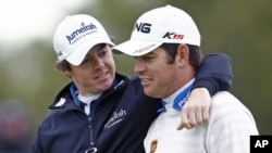Rory McIlroy (L) of Northern Ireland and Louis Oosthuizen of South Africa talk at the 18th green during the final practice round for the British Open golf championship at Royal St George's in Sandwich, southern England, July 13, 2011