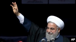 Iranian President Hassan Rouhani waves to the crowd during a rally marking the 39th anniversary of the 1979 Islamic Revolution, in Tehran, Iran, Sunday, Feb. 11, 2018. Hundreds of thousands of Iranians rallied on the streets Sunday to mark the anniversary, just weeks after anti-government protests rocked cities across the country.