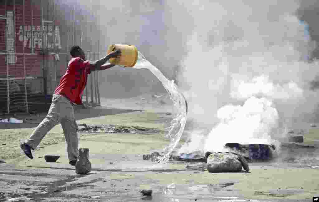 A man throws a bucket of water to put out flames from a tire set on fire in a street by rioting youths, Mombasa, Kenya, Oct. 4, 2013.