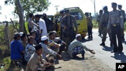 Students are temporarily detained by police officers as they try to leave near an Islamic boarding school where an explosion went off, in Sanolo village, Sumbawa island, Indonesia, July 12, 2011