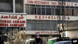 一名阿富汗男子骑车路过喀布尔的中国商品贸易中心(2013年1月22日)。