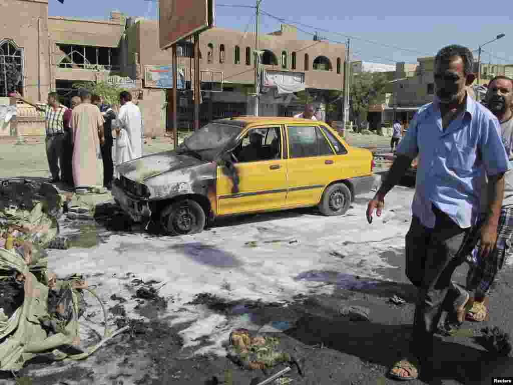 A man walks near the site of a car bomb attack in Baghdad's Hurriya District, August 28, 2013.