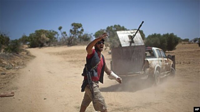 A rebel fighter gives orders to comrades at the front line between the rebels and Moammar Gadhafi forces, 25 km west from Misrata, Libya, May 26, 2011