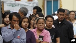 Thai people queue up at a polling center to vote in Thailand's general election in Bangkok, Thailand, July 3, 2011.