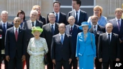 U.S. President Barack Obama, front left, and French President Francois Hollande, front center, stand with Britain's Queen Elizabeth II, second left, and Russian President Vladimir Putin, front right, and other leaders, for a group photo in the 70th anniversary of D-Day in Benouville in Normandy, France, Friday, June 6, 2014. (AP Photo/Charles Dharapak)