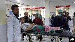 Des agents de santé afghans conduisent un Afghan blessé à l'hôpital après une attaque suicide revendiquée par des talibans à Kaboul, en Afghanistan, 19 avril 2016 (AP Photo / Rahmat Gul)