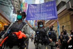 Police display a public announcement banner showing the warning to protesters in Causeway Bay before the annual handover march in Hong Kong, Wednesday, July 1, 2020.
