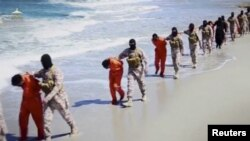 FILE - Islamic State militants lead what are said to be Ethiopian Christians along a beach in Wilayat Barqa, in this still image from an undated video made available on a social media website on April 19, 2015.