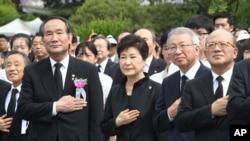 박근혜 한국 대통령(가운데)이 6일 서울 국립서울현충원에서 열린 제61회 현충일 추념식에서 참석자들과 함께 국기에 대한 경례를 하고 있다.