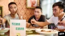 """中國河北邯鄲市一家餐館桌子上立有""""節約糧食杜絕浪費""""的牌子。 (2020年8月13日)"""