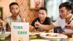 """中国河北邯郸市一家餐馆桌子上立有""""节约粮食杜绝浪费""""的牌子。(2020年8月13日)法新社"""