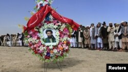 A portrait of former Taliban minister Maulvi Arsala Rahmani, a senior member of the High Peace Council, is seen as officials and mourners attend his funeral in Kabul.