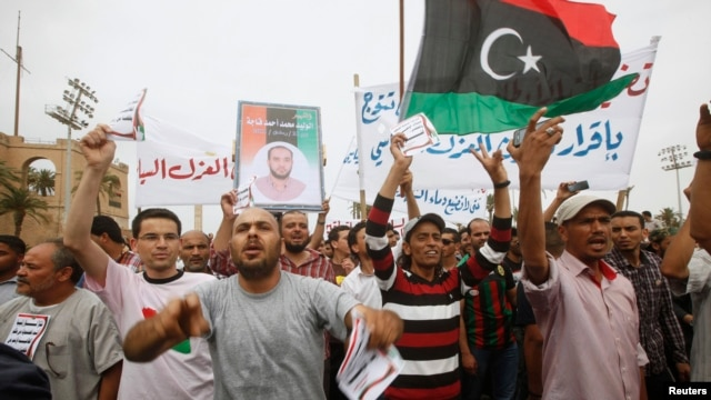 Protesters wave a Libyan flag as they demonstrate in Martyrs' Square demanding that Gadhafi-era officials be banned from taking up political posts, in Tripoli, Libya, May 5, 2013.