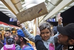 A migrant girl holds a sign expressing her love to Germany as she arrives at the train station in Saalfeld, central Germany, Sept. 5, 2015.