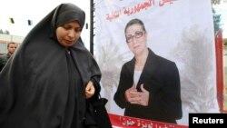 Une Algérienne devant une affiche électorale de Louisa Hanoune, candidate à l'élection présidentielle de 2014, le 27 mars 2014.
