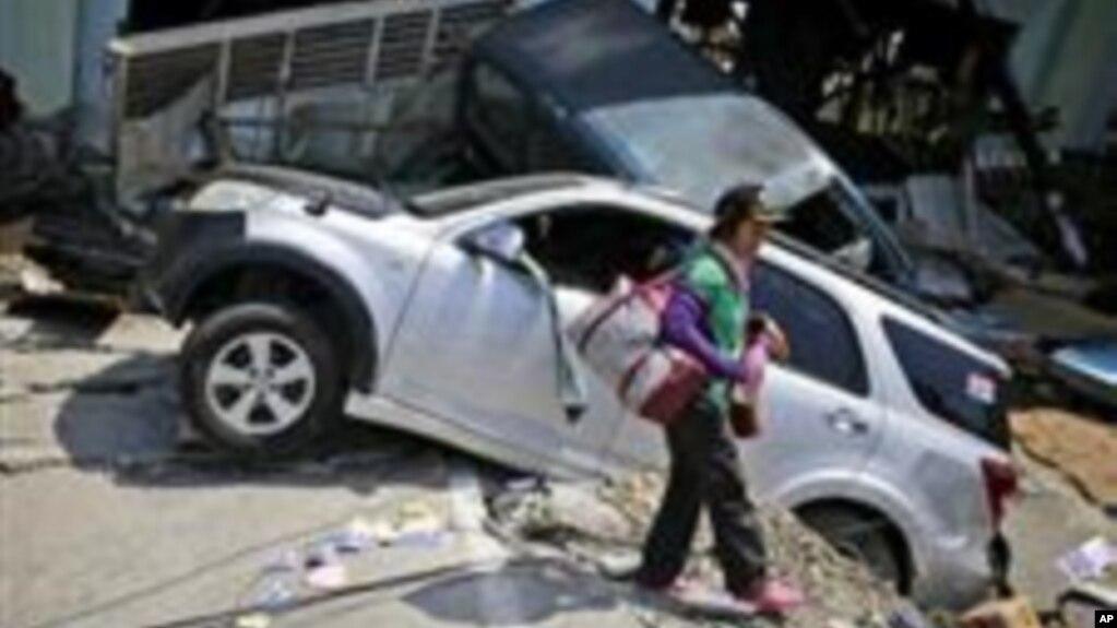 Una mujer pasa cerca de los restos de automóviles arrasados por el terremoto del viernes 28 en el vecindario de Balaroa en Palu, Sulawesi Central, Indonesia, el martes 2 de octubre de 2018.