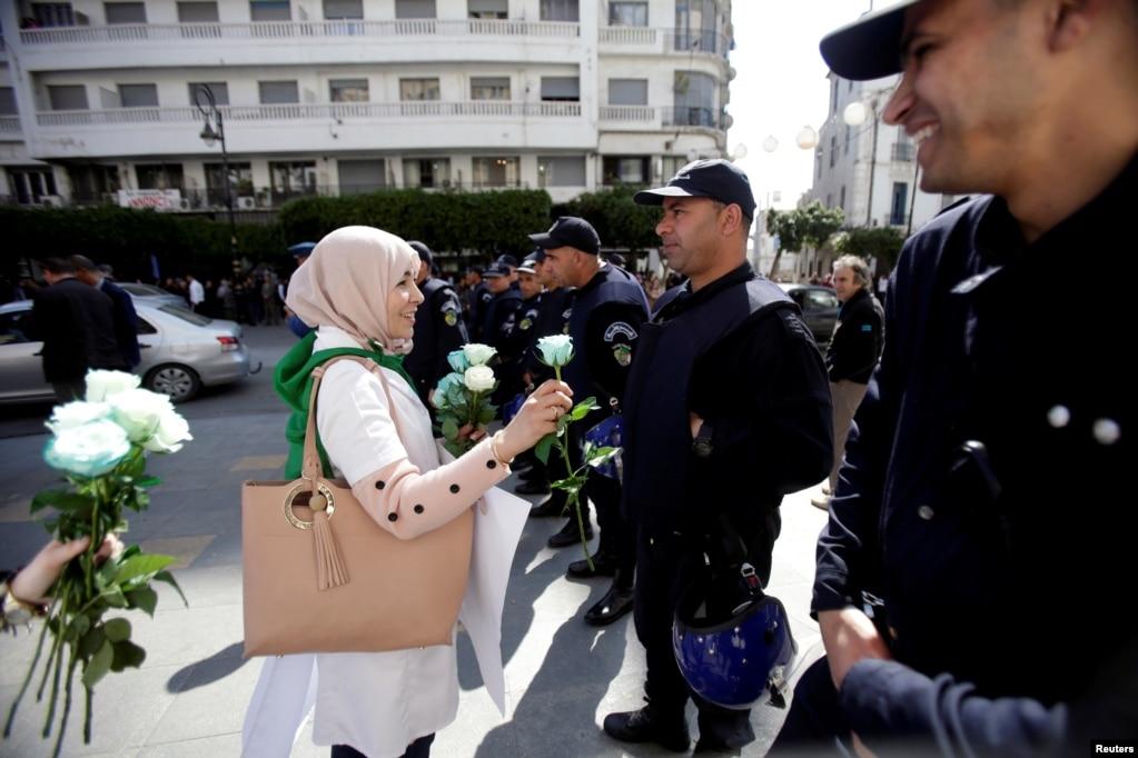 알제리 알제에서 열린 정치 변화 요구 시위 현장에서 시위에 참가한 여성이 경찰들에게 꽃을 나눠주고 있다.