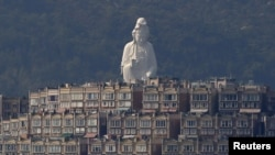 A 76-meter-high (249-feet) bronze-forged white Buddhist Avalokitesvara or Guan Yin statue, part of the Tsz Shan Monastery, stands behind luxurious houses at Taipo district in Hong Kong April 16, 2015.