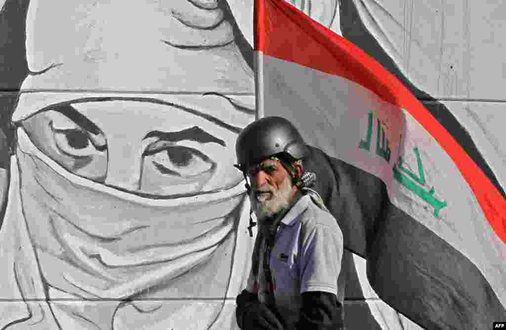 An Iraqi protester carrying his national flag walks past graffiti during ongoing anti-government protests, at Tahrir square in the capital Baghdad.