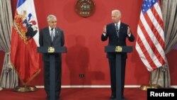 En el palacio presidencial de La Moneda, el vicepresidente Joe Biden, derecha, resalta la democracia y el libre mercado como la clave del éxito en Chile.