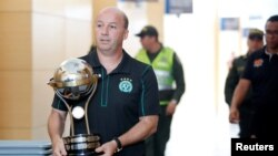 Marcelo Zolet, asesor legal del club brasileño de fútbol Chapecoense lleva una réplica del trofeo de la Conmebol tras recibirlo de los directores del club colombiano Santa Fé, el último campeón de la Copa Sudamericana en Medellín, Colombia.
