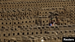 A laborer carries bricks at a kiln in Karjat, India, March 10, 2016. Thousands of brick kiln workers in India's western Maharashtra state are learning from activists that they have the right to a minimum wage, basic amenities and fair treatment - but remain in debt bondage to owners who deny them these rights with impunity.