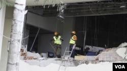 Para petugas memeriksa gedung PBB di Abuja, Nigeria yang rusak parah akibat ledakan bom mobil (26/8).