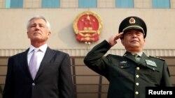 El secretario de Defensa de Estados Unidos, Chuck Hagel y su contraparte china Chang Wanquan escuchan el himno nacional chino, en Beijín.