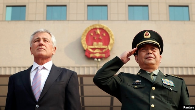 FILE - US Defense Secretary Chuck Hagel (L) and his Chinese counterpart Chang Wanquan (R) listen to the Chinese national anthem during a welcoming ceremony at the Chinese Defense Ministry headquarters, prior to their meeting in Beijing, April 8, 2014.